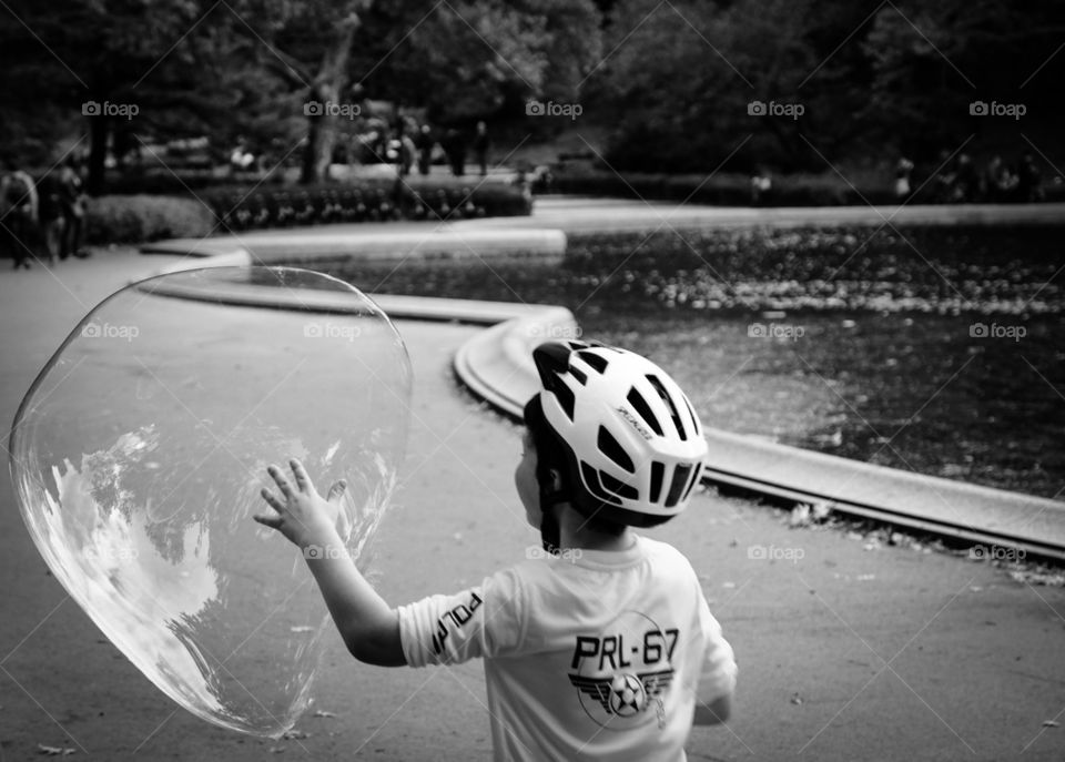 Boy Chasing Bubble In Park, Young Boy With Bubble In Central Park, Summertime Fun With Bubbles, Monochromatic Portrait Of Young Child In Central Park