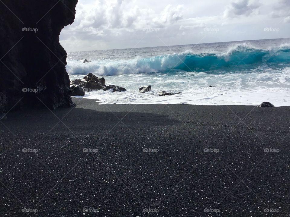 Wave meets black sand beach