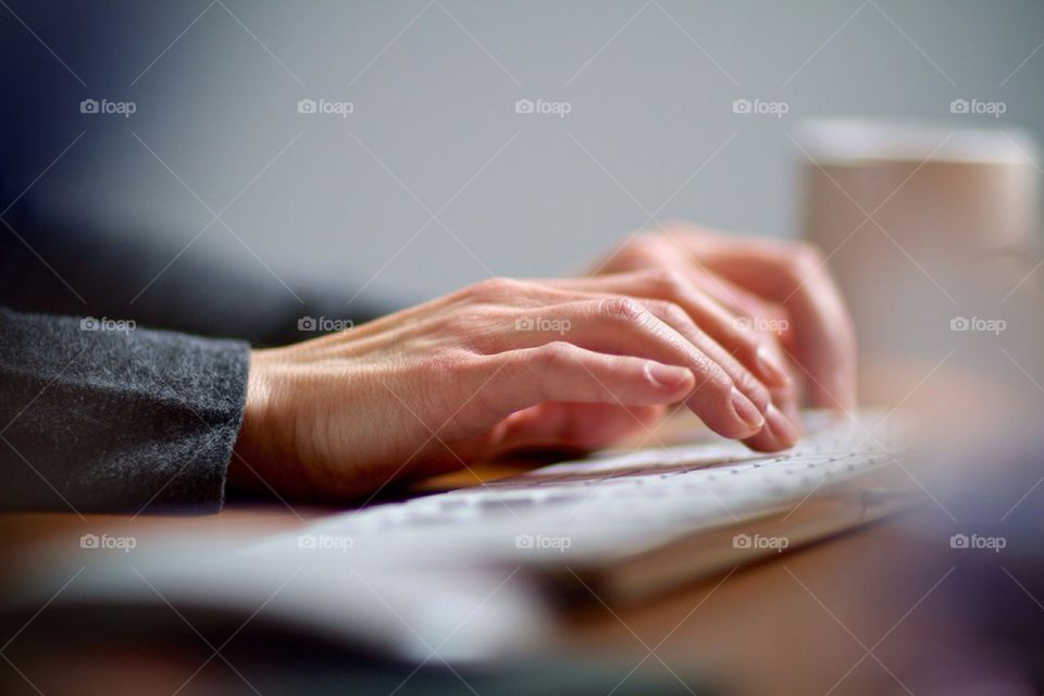 Female hands typing on a computer keyboard working in her office.