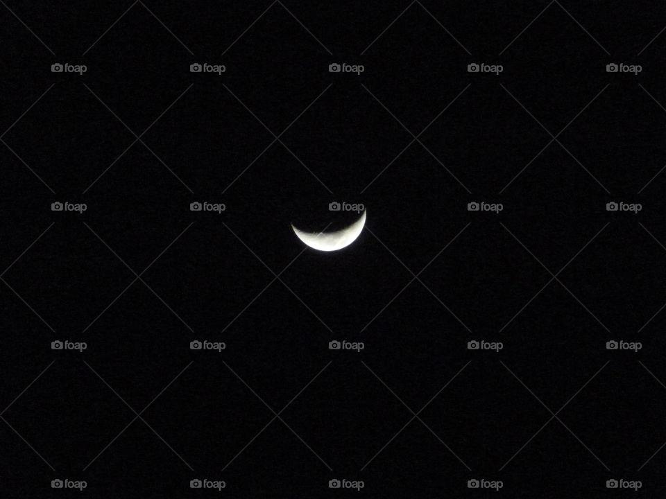 Crescent moon in dark sky