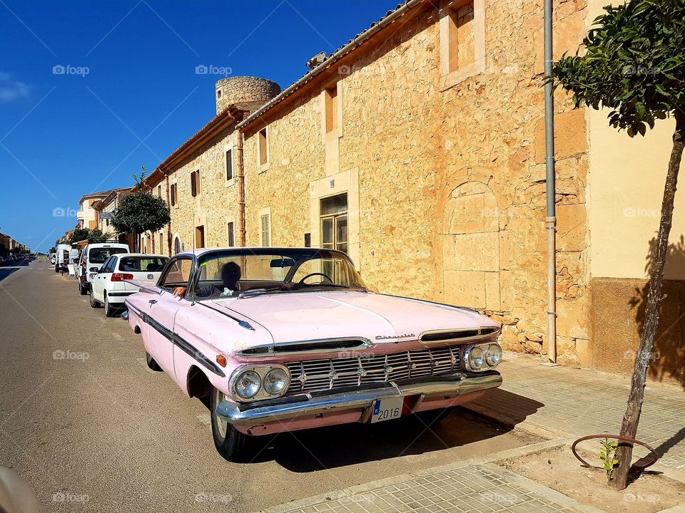 a pink chevrolet classic car / oldtimer on the streets of Mallorca. it seems if time has stopped