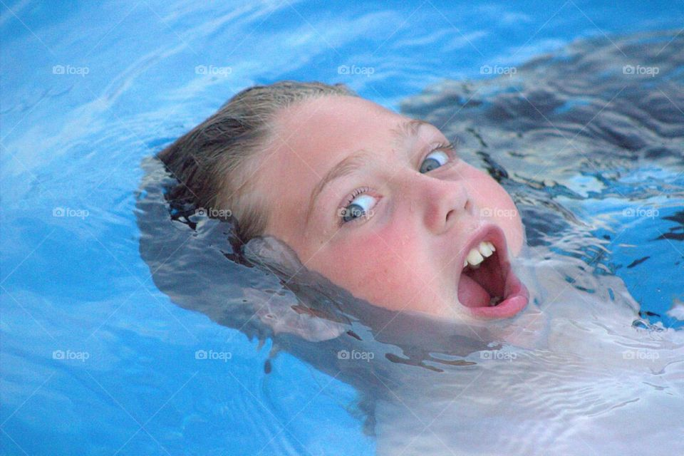 A goofy young girl getting a mouthful of pool water as she floats on her back.