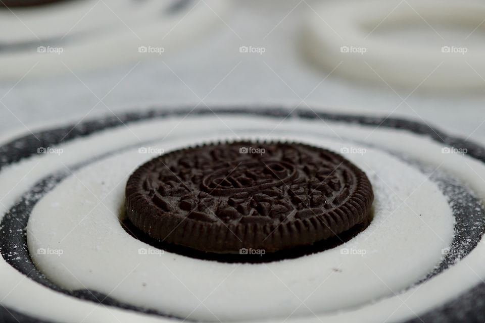 Adding the finishing touch to a cake .. iced in black and white and the centre circle being an Oreo Biscuit