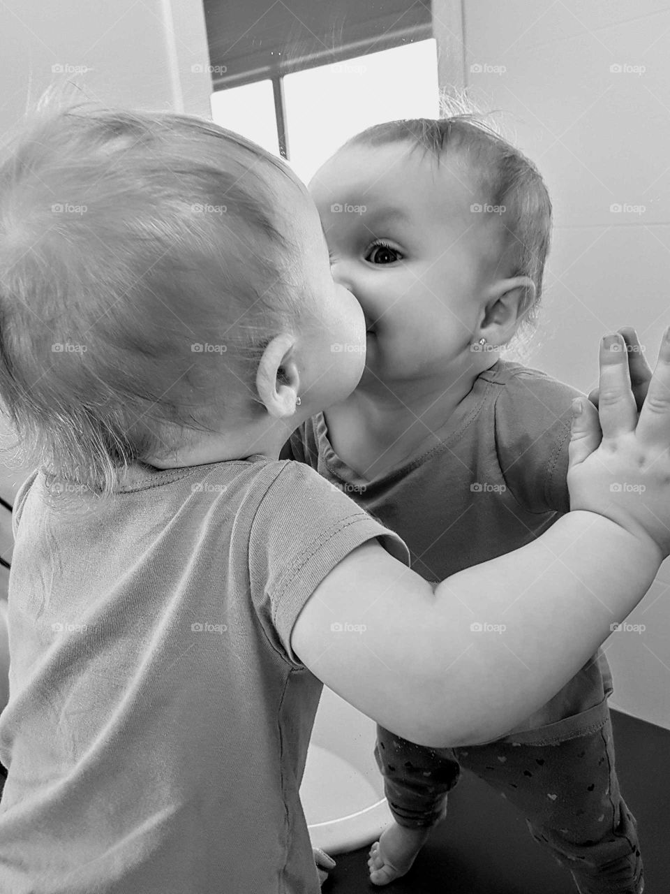Baby kissing her reflection in mirror