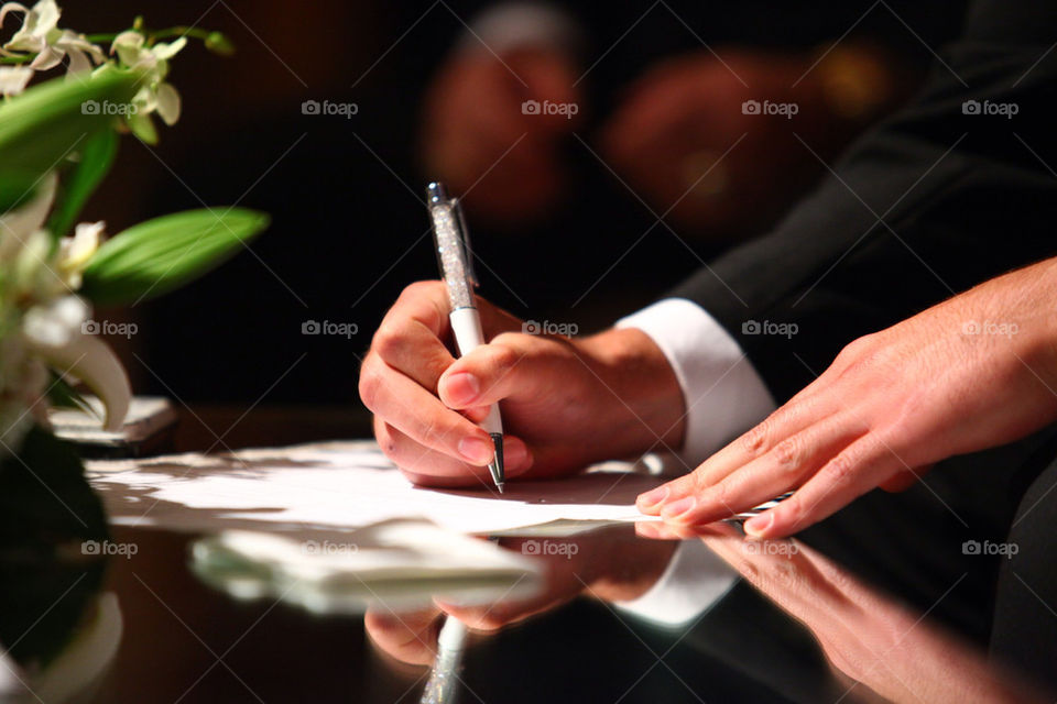 Man in suit signing documents, contract