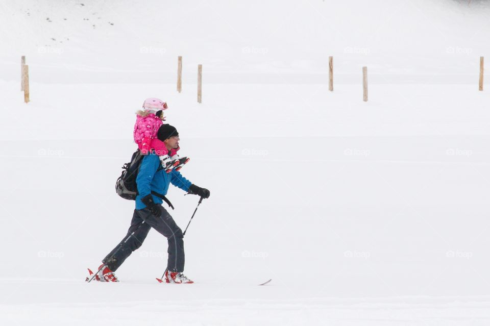 Happy Father Skiing With His Daughter Sitting On His Shoulders