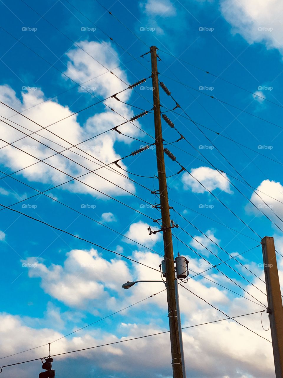 Power lines in the clouded blue sky
