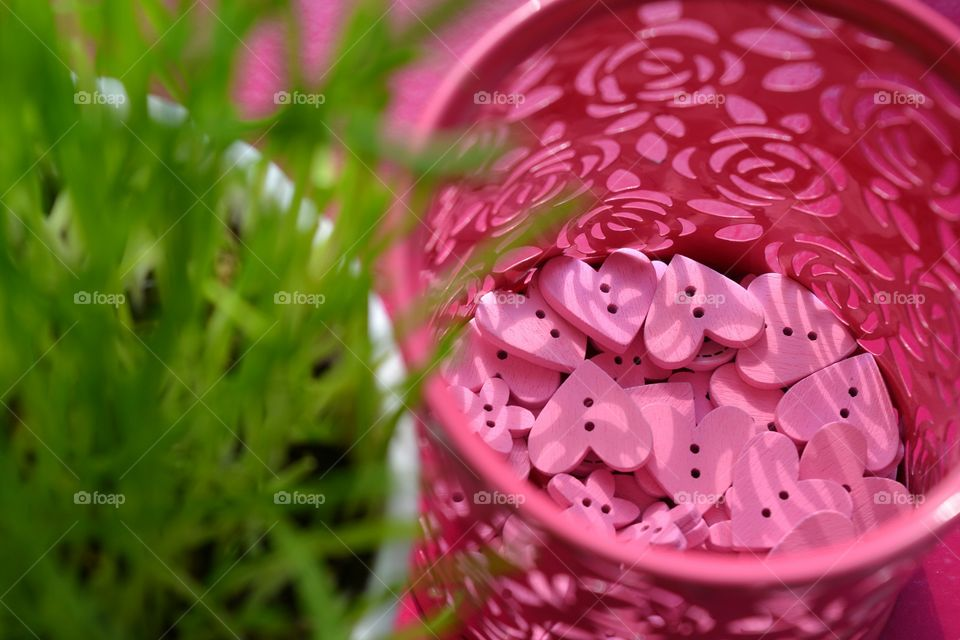 pink color wooden buttons hearts and flowers green grass background