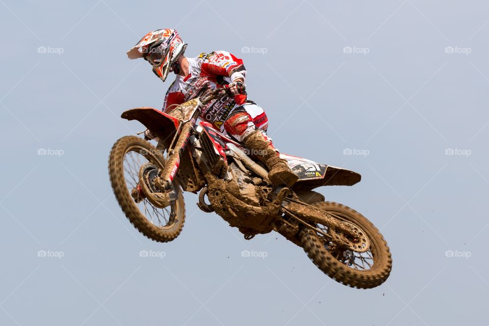 Motorcycle high up in the air. Motocross motorcycle jumps high in the air. Rider has white and red clothing. Motorcycle is dirty and covered with mud