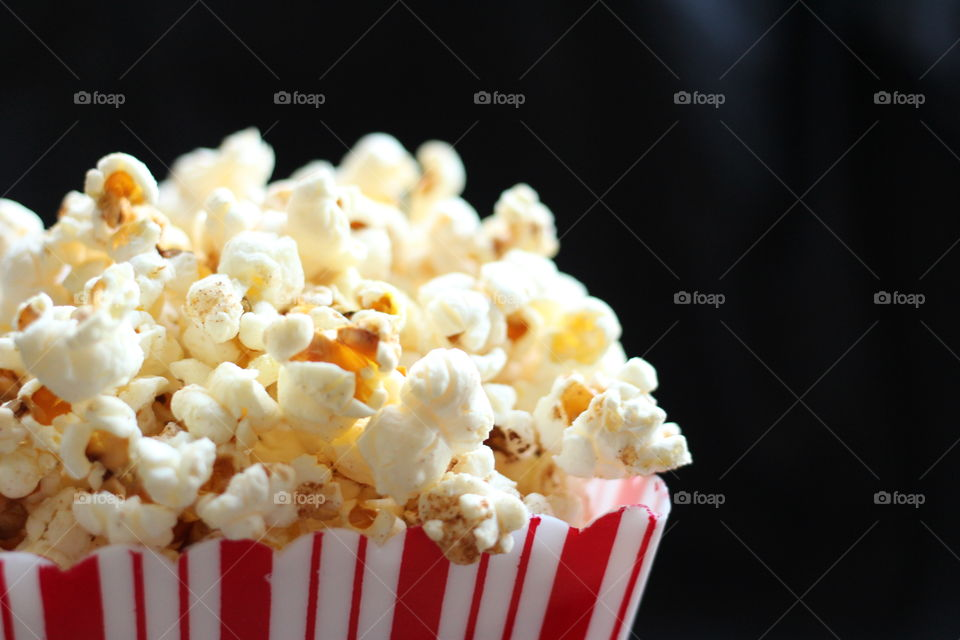Popcorn in stripy box. Close-up of popcorn in a red and white striped box on a black background
