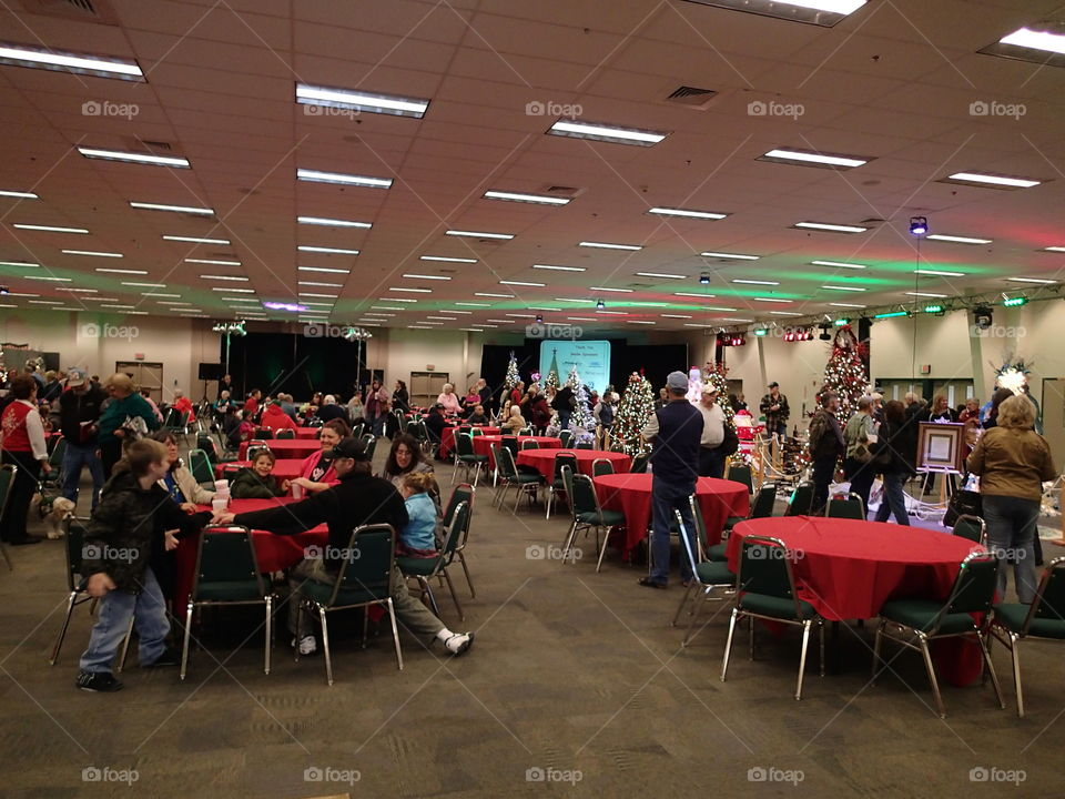 Tables full of people amongst the trees at a Christmas tree decoration event for charity.