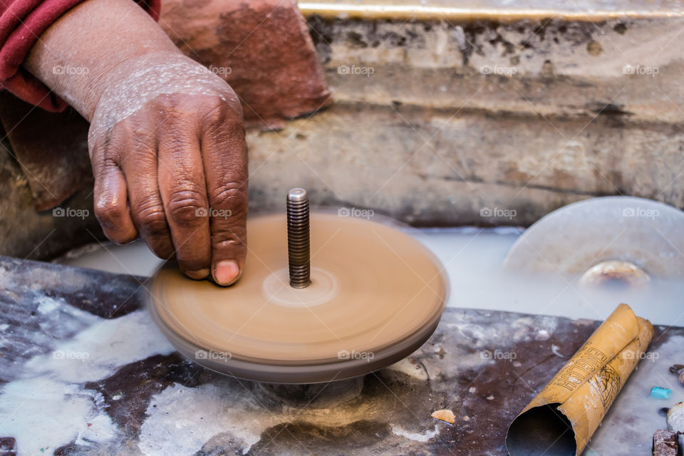 This man's job is to use this machine to turn big stones into lovely little soft and clear pieces of gems, to be used later as accessories or part of decoration. You will see different angles of the same hand and job.