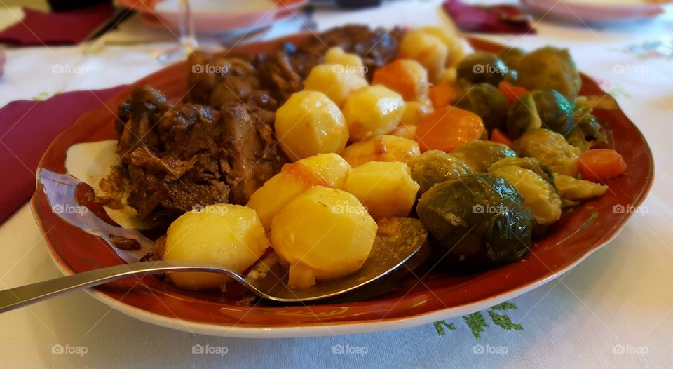 New Year's Day dinner. Roast lamb with potatoes, Brussels sprouts and carrots.