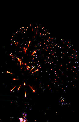 Illuminated firework display against sky at night