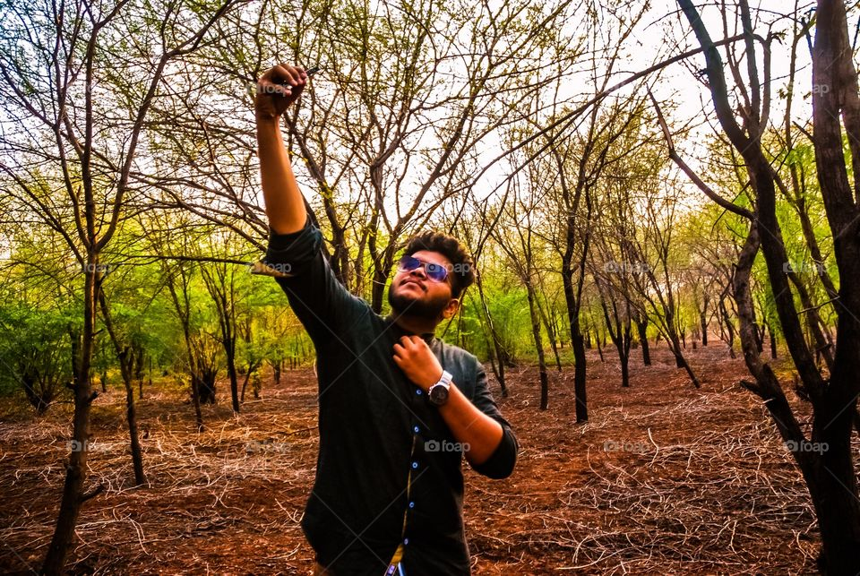 Guy taking selfi using mobile camera  in forest