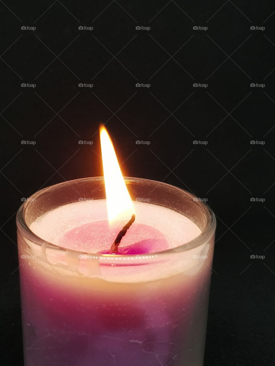 Candlelight in the dark. The outer side of candle is glass and texture colour is pink, white pink.