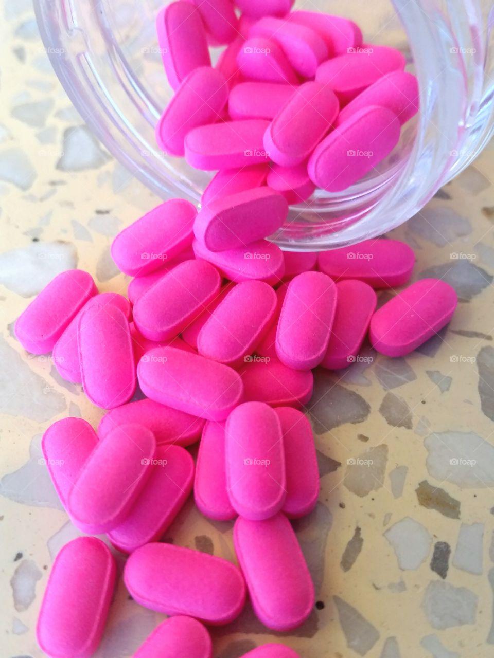 Pink pills tumbling out of jar