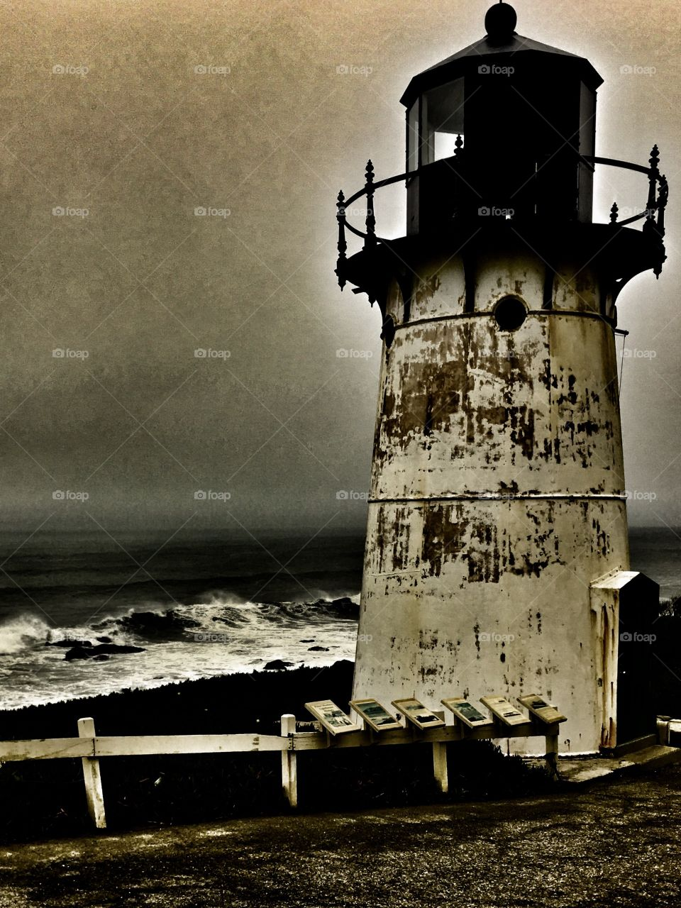 Stormy seas and a lighthouse all in black and white.