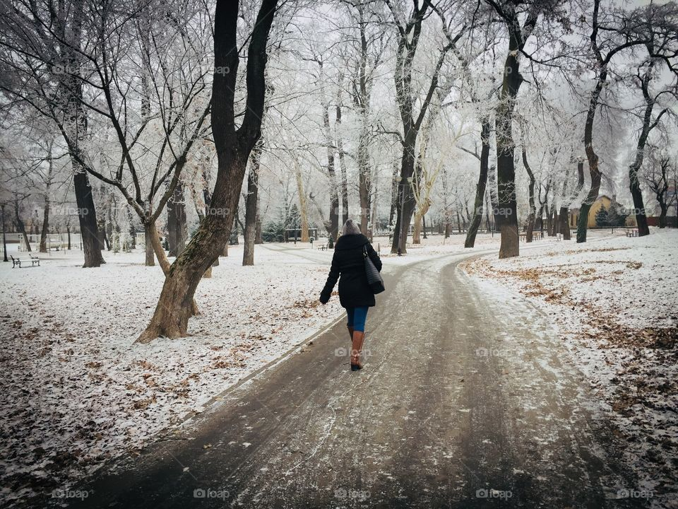 Woman walking alone in the park in winter