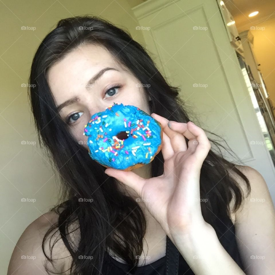 Young woman holding donut in hand