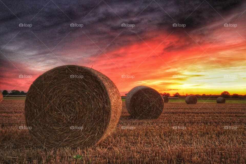 Bails of hay sit in a farmers field at sunset with a dramatic sky overhead.