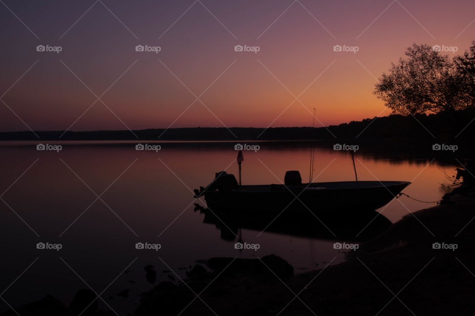 A tied boat floats perfectly still during the vivid twilight period just before sunrise. Rollingview State Park near Raleigh North Carolina.
