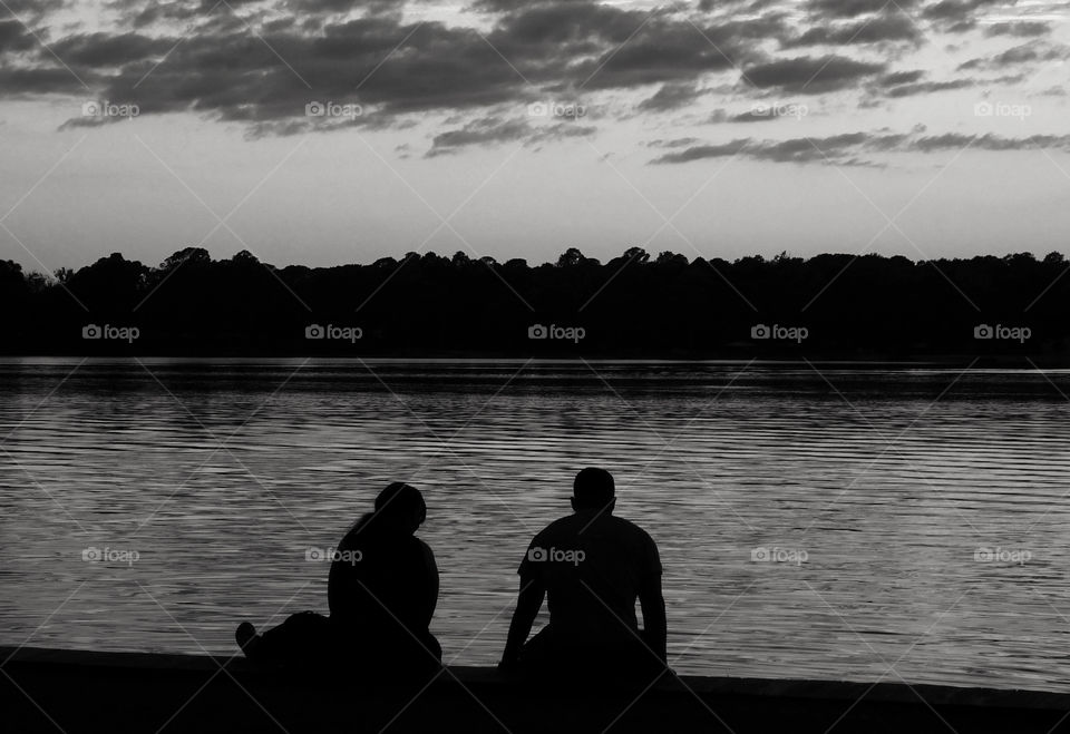 Black and White Sunset photo. A couple sitting on the dock of the bay having a lively discussion.