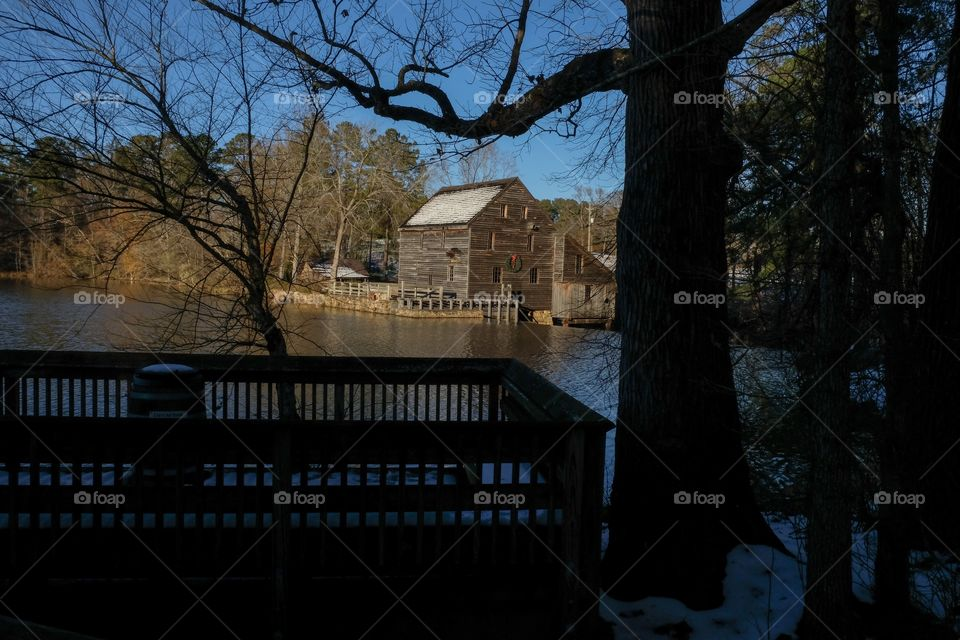 Late afternoon view with the sunshine falling upon the old gristmill with snow on the roof across the millpond, with the silhouettes of a barren oak tree and an observation deck at Yates Mill County Park in Raleigh North Carolina.
