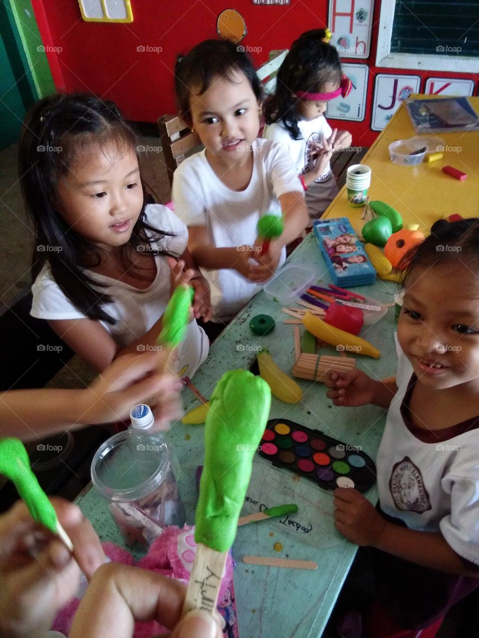 Children making popsicle with clay