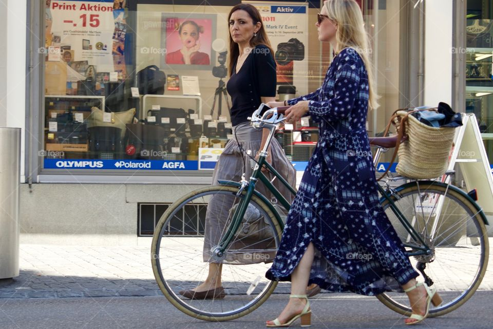 Two Women Walking With  A Bike In A Paved Street Of Zürich