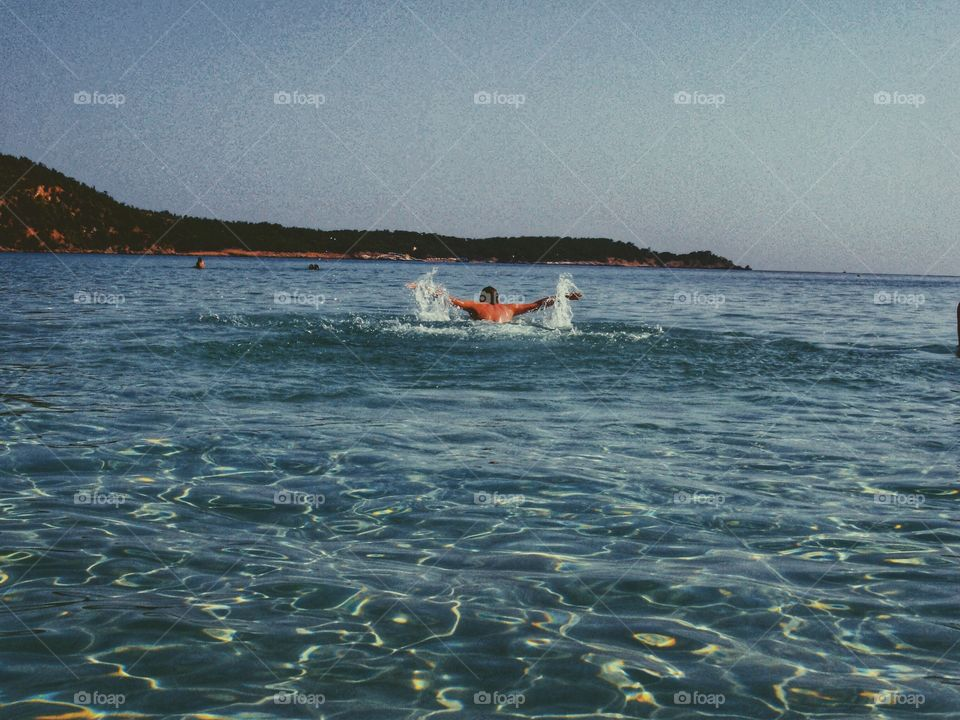 Swimming in the ocean on the summer holiday. Vacation time with family and friends.