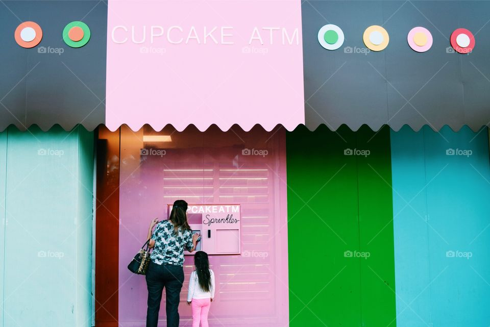 Mother and daughter standing in front of cupcake shop