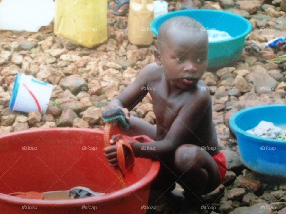 African Boy Washing Shoes