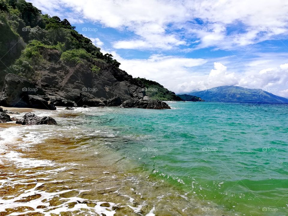 """Sandy lonely tropical beach on island """"Mindoro"""" surrounded by tropical rainforest in the Philippines"""