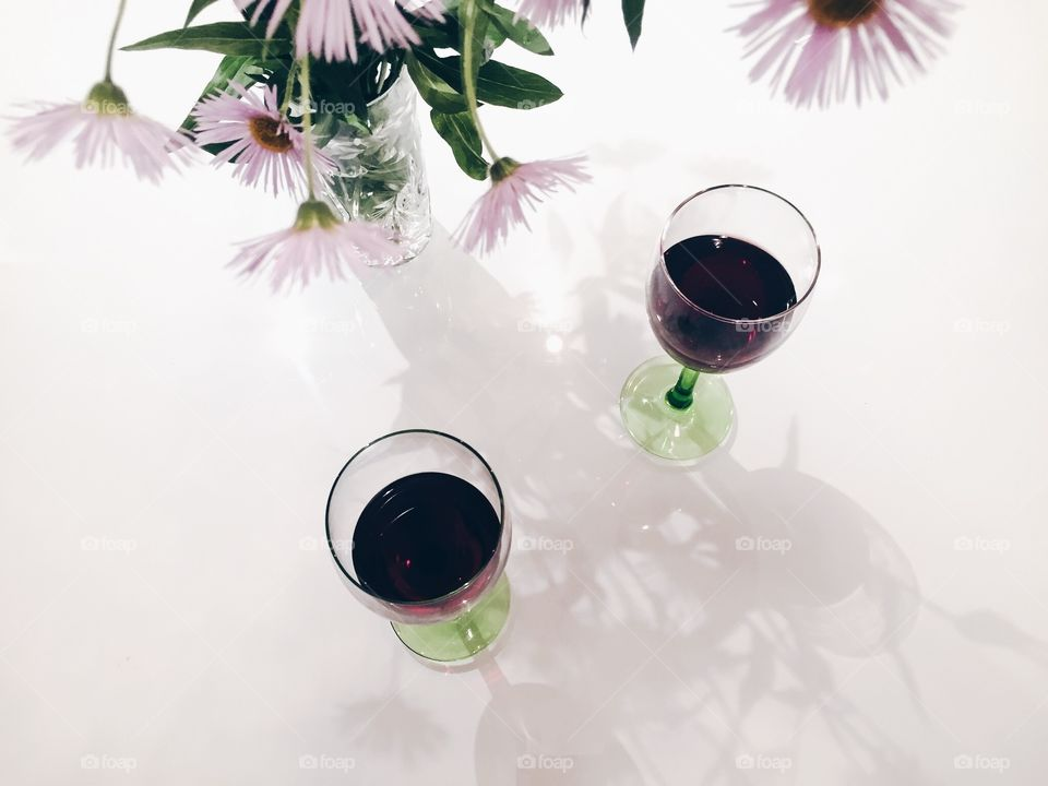 Two glasses with red wine and vase of flowers in harmony in color