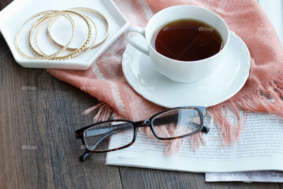 Cup of coffee with eyeglasses and bangles on table