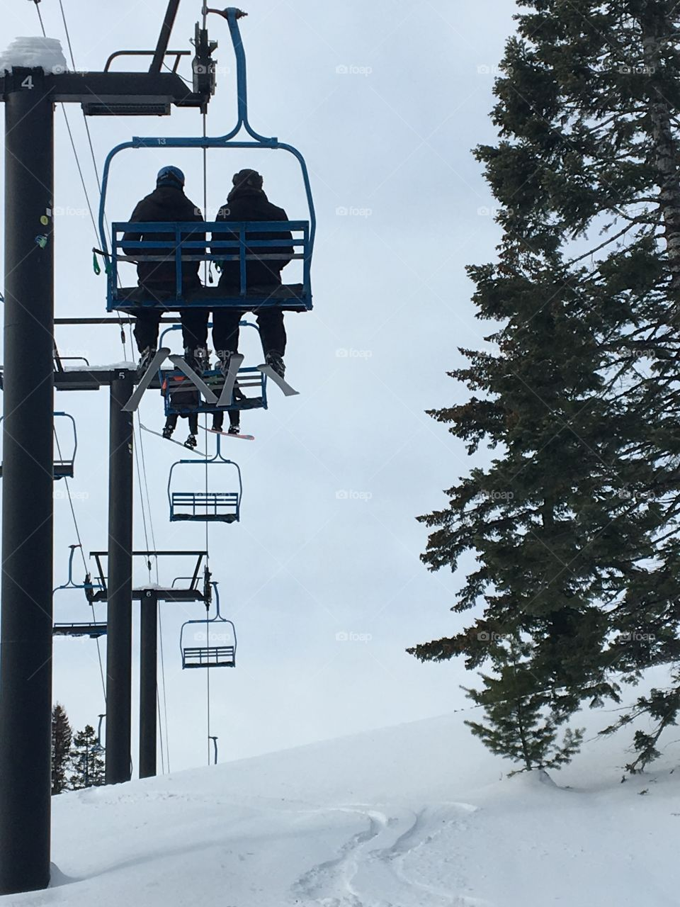 Two skiers on a ski lift